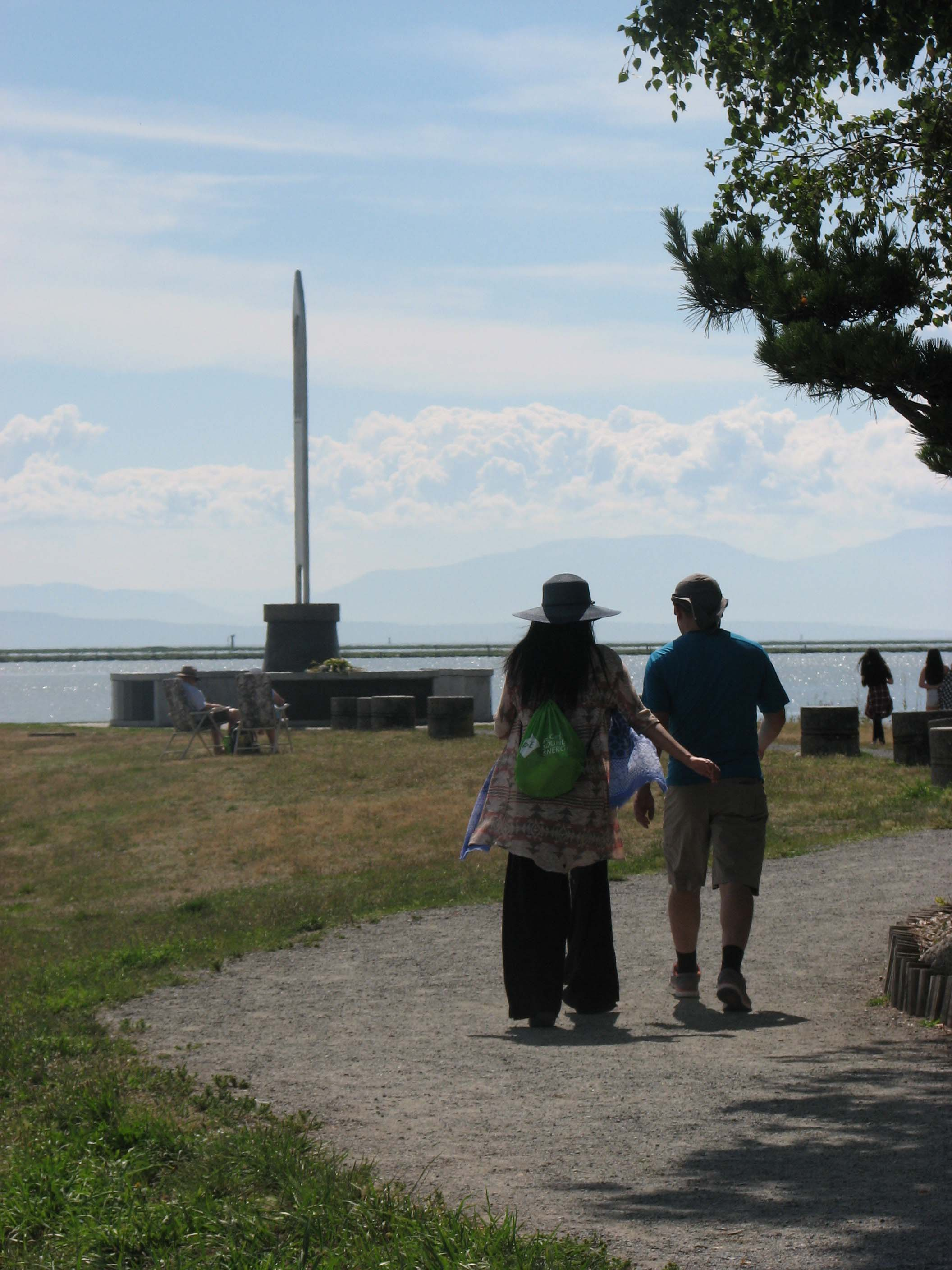 People walking the path in Garry Point Park pass by Fisherman's Memorial